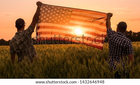 Two men energetically raised the US flag in a picturesque field of wheat #1432646948