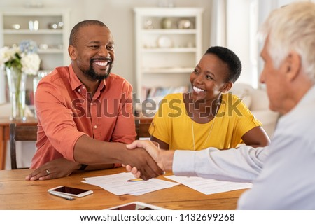 Mature black husband shaking hands with senior agent on taking loan. Happy african couple sealing with handshake a contract with financial advisor for investment. Man making sale purchase deal. #1432699268