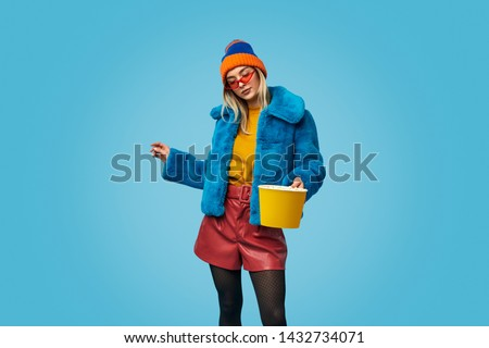 Weird young female in colorful trendy outfit holding bucket of popcorn during showtime against blue background #1432734071