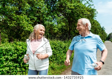 cheerful woman with grey hair looking at husband while holding bottle and running in park  #1432735925