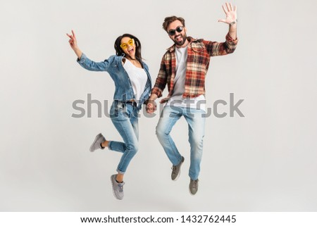 happy smiling couple isolated active jumping on white studio background, stylish mand and woman in casual denim hipster outfit wearing shirt and sunglasses having fun together, dating friends #1432762445