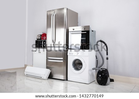 Set Of Household Kitchen Electronics Appliances On Reflective White Floor Against Wall #1432770149