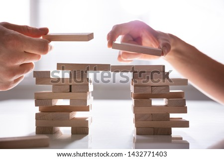 Close-up Of Human's Hand Placing Wooden Block Over Desk #1432771403