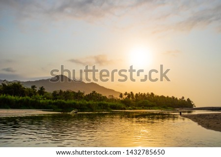 A wide river flows through the tropical rainforest of South America in a delta at a beautiful sunset where people bathe and enjoy life in Colombia Palomino #1432785650