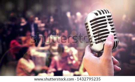 Microphone and singer on stage concept - Close up vintage microphone in singer hand singing on stage of wedding event party or business meeting with lighting effect and copy space #1432795235