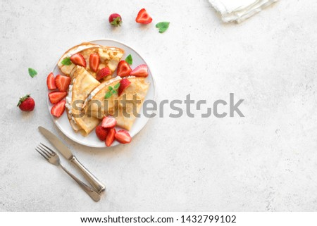 Crepes with ricotta cheese and fresh strawberries on white background, top view, copy space. Delicious crepes, thin pancakes. Royalty-Free Stock Photo #1432799102