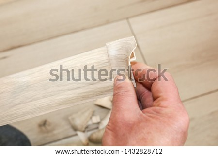 Man is installing the baseboard. Repair works indoors. Renovation in the flat. #1432828712