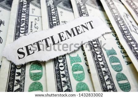 Settlement newspaper headline on money                              Royalty-Free Stock Photo #1432833002