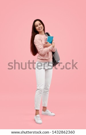 Full body happy teen student with notebooks and backpack smiling and looking at camera while standing against pink background
