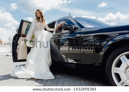 Stylish Bride with Flower Bouquet near Limousine. Pretty Young Woman Dressed White Wedding Dress and Jewelry Diadem with Veil. Girl Holding Roses Bunch and Standing near Black Car. Outside Photo #1432898384
