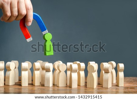 A hand with a magnet pulls green human figure out of the big crowd of people. Recruiting new workers, headhunters. Search for talented workers Labor migration, the demand for good specialists. #1432915415