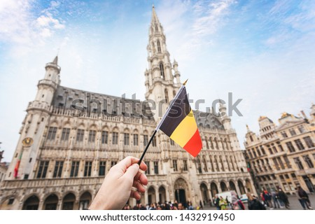 Woman tourist holds in her hand a flag of Belgium against the background of the Grand-Place Square in Brussels, Belgium. Traveling in Belgium, the main attraction of Brussels, the Grand Market Square #1432919450