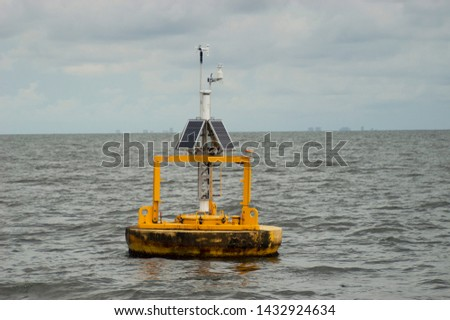 Solar powered buoy in the Gulf of Mexico off the coastline of Orange Beach, Alabama during the summertime measuring oceanographic parameters such as humidity, wind direction and velocity. Royalty-Free Stock Photo #1432924634