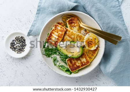 keto ketogenic diet soft boiled eggs with grilled haloumi, avocado and lettuce, mediterranean cuisine on pastel background Royalty-Free Stock Photo #1432930427