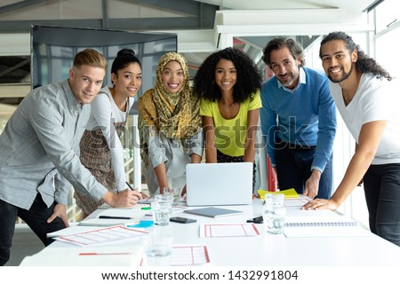 Front view of diverse business people looking at camera while working together at conference room in a modern office Royalty-Free Stock Photo #1432991804