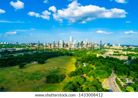 Austin Texas skyline cityscape aerial drone view above green landscape Barton creek flowing into town lake #1433008412