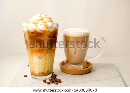 Ice coffee in the glass topped whipping cream with coffee beans. Cold summer drink on wooden background and copy space. Advertising for caramel mocha and chocolate beverage for the cafe. Royalty-Free Stock Photo #1433030078