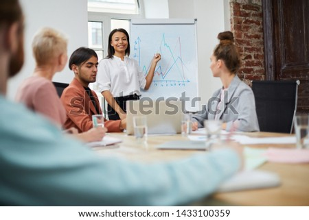 Portrait of mixed race businesswoman standing by whiteboard and giving presentation to colleagues during meeting in conference room, copy space #1433100359