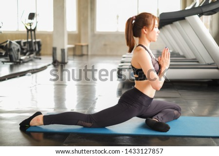 portrait asia woman working out or exercise and wearing sportswear in fitness or gym center, practicing yoga concept with blur running treadmill background #1433127857