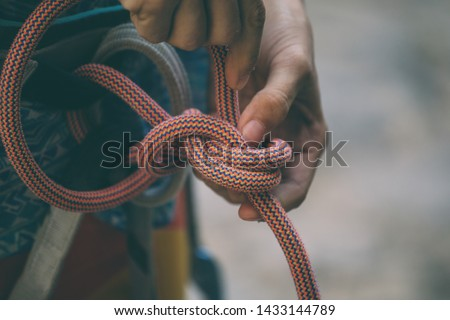 Rock climber tying a safety knot. A girl is checking equipment for climbing. A woman is preparing for the ascent. Rope for insurance. #1433144789