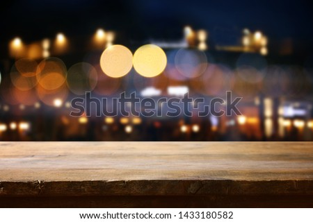 background of wooden table in front of abstract blurred restaurant lights #1433180582