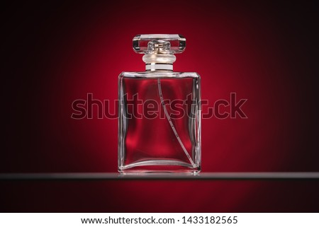 Perfume glass bottle on red background