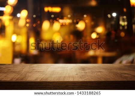 background of wooden table in front of abstract blurred restaurant lights #1433188265