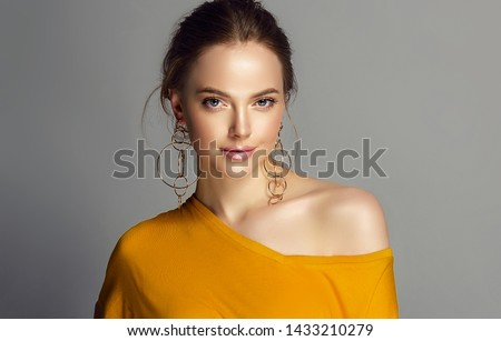 Beautiful girl in orange blouse on one shoulder . Fashionable and stylish women's clothing . Fashion look  , beauty and style. Young woman in trendy jewelry earrings rings.  #1433210279