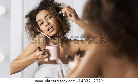 Afro-american girl in hurry put on makeup, drinking coffee and talking by phone simultaneously in front of mirror in bathroom. Sorry, I am late today concept #1433212022