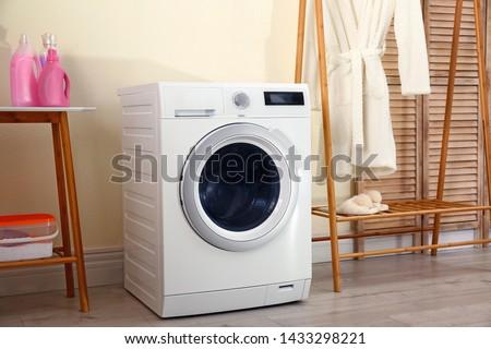 Laundry room interior with modern washing machine #1433298221