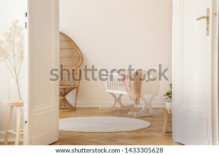White open double door in elegant apartment with nursery designed with white crib and wicker peacock chair, real photo with copy space Royalty-Free Stock Photo #1433305628