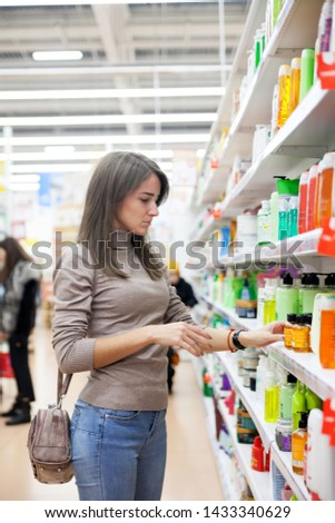 Young woman choosing   skin care product in   store. #1433340629