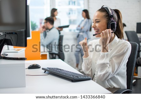 Cheerful young female technical support agent holding fist up and celebrating successful finish of work with client in call centre. Concept of well done work in customer support center. #1433366840