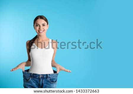 Attractive young woman with slim body wearing her old big jeans on color background. Space for text Royalty-Free Stock Photo #1433372663