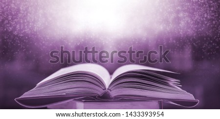 The blurred book that is bewitched with magic, the magic light in the dark, with the bright light shining down as the power to search for knowledge. For research and use as a blurred background #1433393954