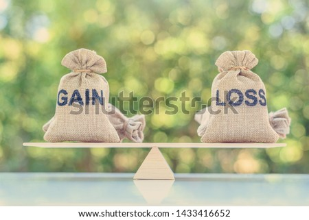 Capital investment gain and loss, financial concept : Gain and loss bags on a basic balance scale, depicts balancing between profit and loss while managing assets e.g bonds, stocks, derivatives, ETFs #1433416652