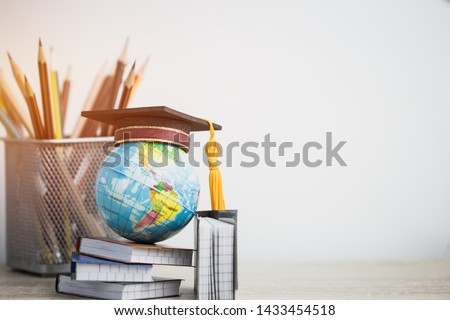 Concept of global business study abroad education. Graduation hat on models globe, books with pencils on wood white background. Congratulations to graduated, Studies lead to success. Back to School #1433454518