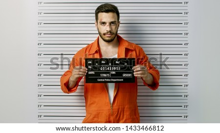 In a Police Station Arrested Man Getting Front-View Mug Shot. He's Wearing Prisoner Orange Jumpsuit and Holds Placard. Height Chart in the Background. #1433466812