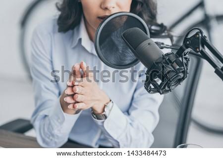 cropped shot of radio host speaking in microphone in broadcasitng studio #1433484473