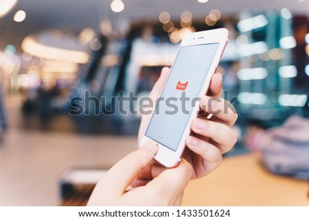 CHIANG MAI, THAILAND - May.10,2019: Woman hands holding Apple iPhone with tmall apps on the screen. #1433501624