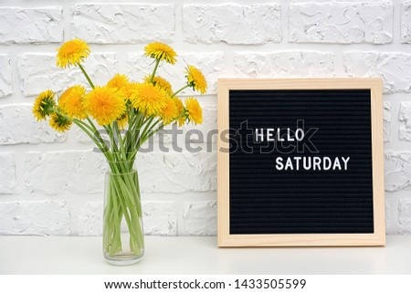 Hello Saturday words on black letter board and bouquet of yellow dandelions flowers on table against white brick wall. Concept Happy Saturday. Template for postcard.