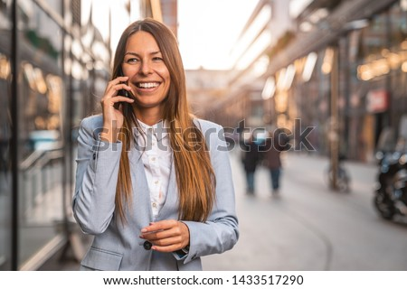 Beautiful business woman using mobile phone while walking on the street - Stock image #1433517290