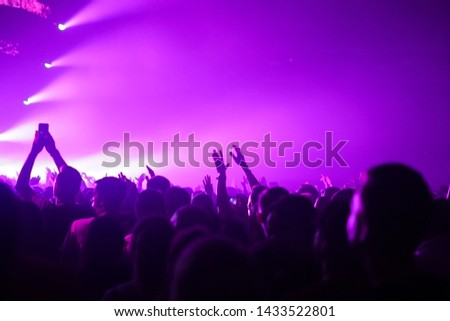 silhouettes of concert crowd in front of bright stage lights #1433522801