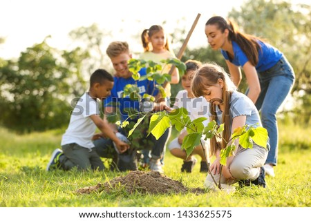 Kids planting trees with volunteers in park #1433625575