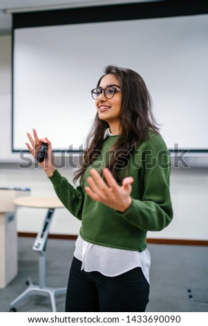 Portrait of a young, beautiful, attractive and intelligent Indian Asian woman wearing spectacles in a sweater giving a presentation in a lecture classroom. She is smiling as she is presenting.  #1433690090