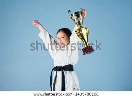 sport success. Training to be the best. small girl with champion cup. martial arts. practicing Kung Fu. happy childhood. winner little girl in gi sportswear. knockout. energy and activity for kids. #1433788106