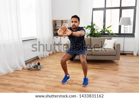 sport and healthy lifestyle concept - indian man with fitness tracker exercising and doing squats at home #1433831162