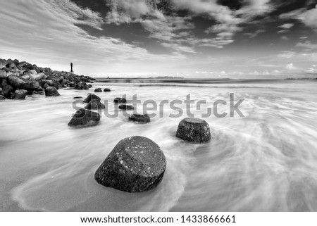 light house on a breakwater at Chendering Beach, located in Terengganu, Malaysia. slow shutter speed,Soft focus effect.black and white photography #1433866661