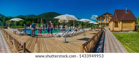 Altai, Lake Aya - Russia: July 18, 2014. Beautiful background and landscape, panorama of a large pool with blue water, with sun loungers, in nature, on site, on a summer day in a mountainous area. #1433949953