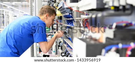 young apprentice worker in an industrial company assembling electronic components in the mechanical engineering of a modern factory  #1433956919